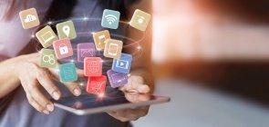 duas mãos segurando um celular. dele saem vários símbolos de redes sociais, wifi e outros ícones relacionados à cultura digital
