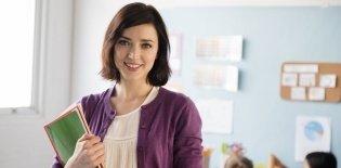 Professora segura cadernos e fichários na sala de aula