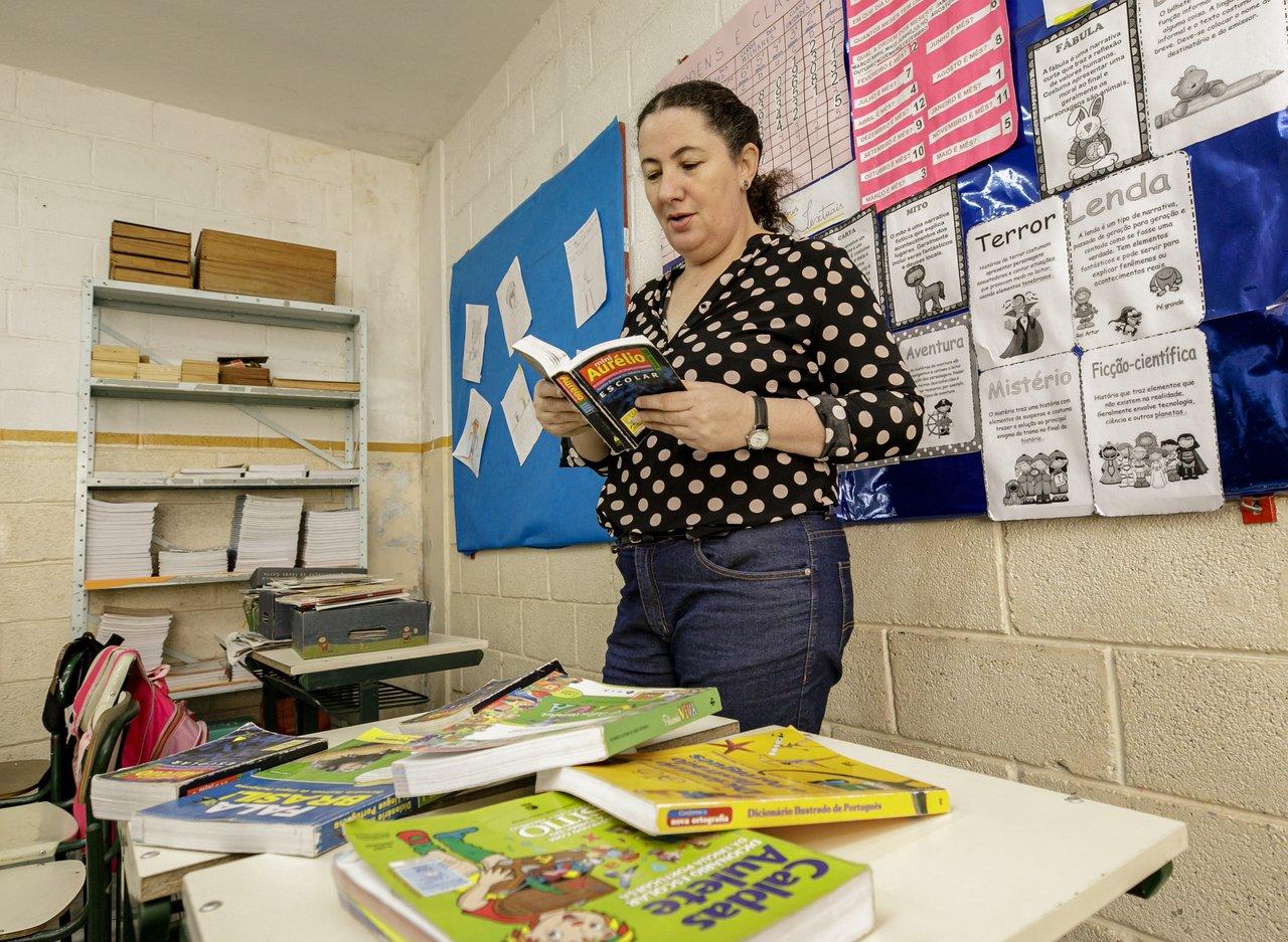 A professora alfabetizadora e articulista da Nova Escola, Mara Mansani, segura um exemplar do dicionário Aurélio em mãos, tendo à frente uma mesa com livros, em uma sala de aula