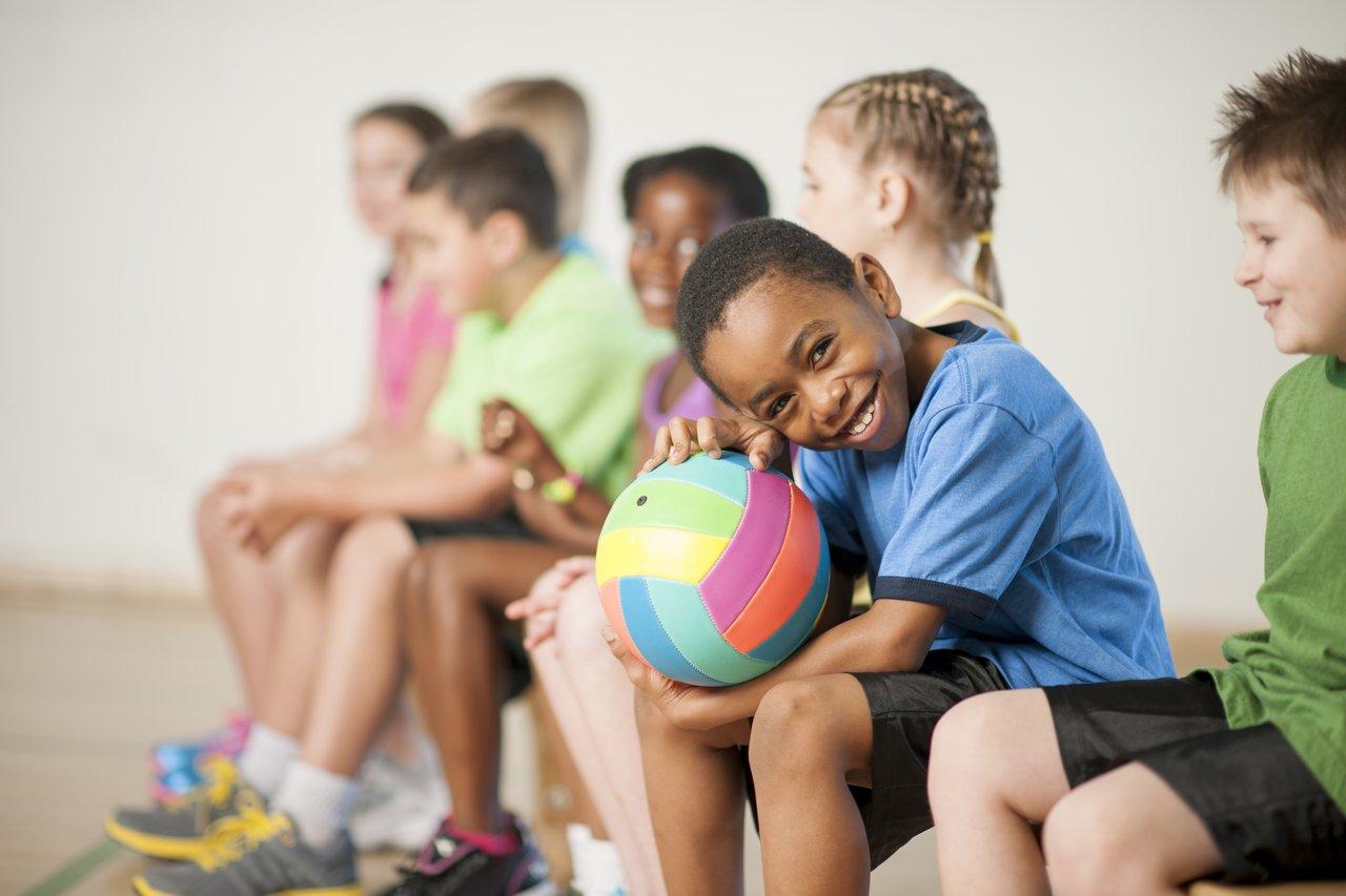 Crianças sentadas em uma quadra coberta sorriem para a câmera com bola na mão