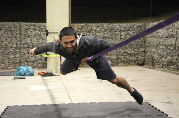 Faça os movimentos da <i>but bounce</i>. Quando a fita impulsionar você para cima, flexione os joelhos e projete o corpo para a frente, para cair deitado na diagonal