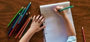 Criança com caderno aberto e dois nomes escritos sobre mesa com lápis espalhados