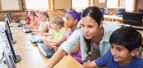 Professora e alunos usam computador na escola