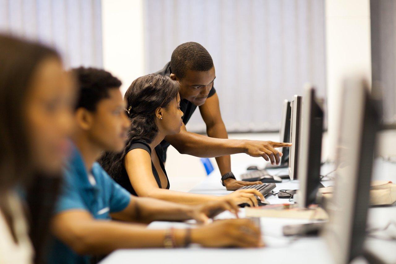 Grupo de alunos em frente a monitores de computadores e professor ao fundo, ajudando uma aluna