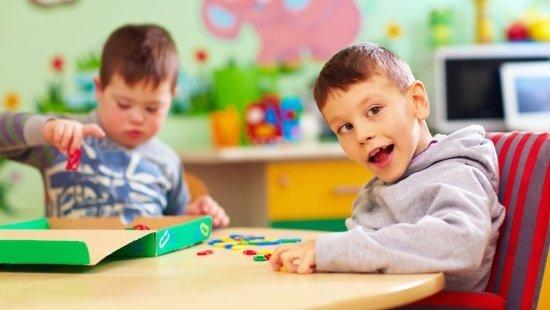 Duas crianças brincam em uma mesa com jogos e brinquedos. Em primeiro plano, uma criança com deficiência intelectual olha em direção ao usuário e sorri. Em segundo plano, um pouco mais desfocada, uma criança com síndrome de Down concentra-se em seu brinquedo.
