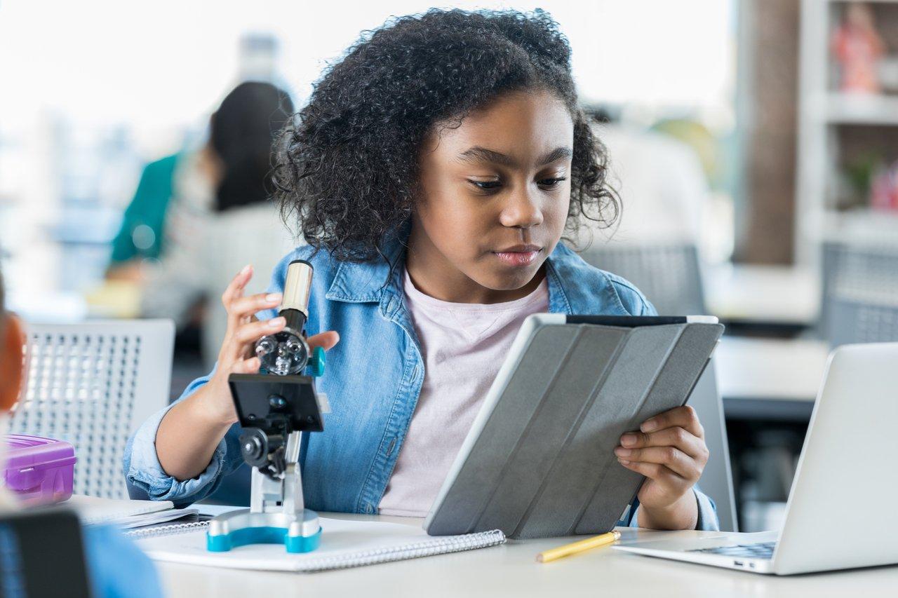 Estudante sentada em bancada lê em tablet e usa um microscópio
