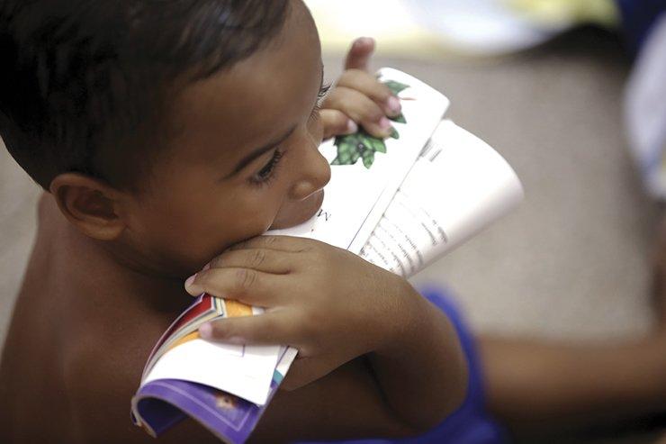 Os pequenos interagem e exploram os livros como podem