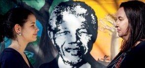 Duas educadoras de perfil se olham. No fundo um desenho do Nelson Mandela