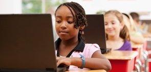 Alunos usam computador em sala de aula