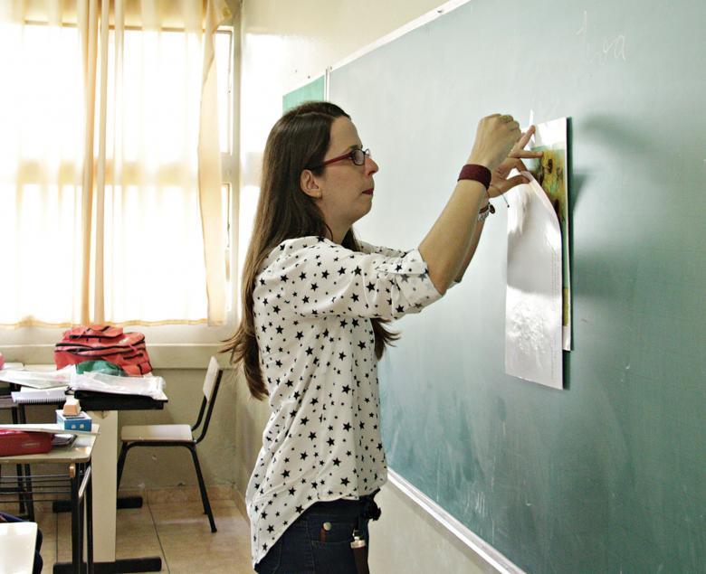 Professora prega um cartaz no quadro