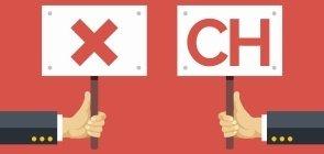 Mãos segurando placas com X e CH