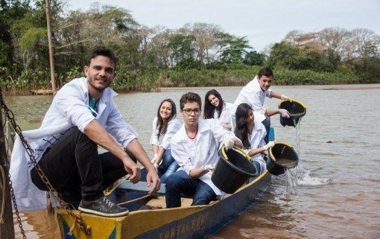 Em um barco no meio do rio, vê-se um barco com o professor Wemerson e cinco alunos. Todos vestem jaleco e três das crianças, seguram um balde com água do rio.