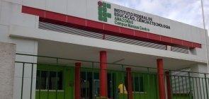 Fachada do prédio do IFAM com colunas vermelhas, grades verdes e muro branco