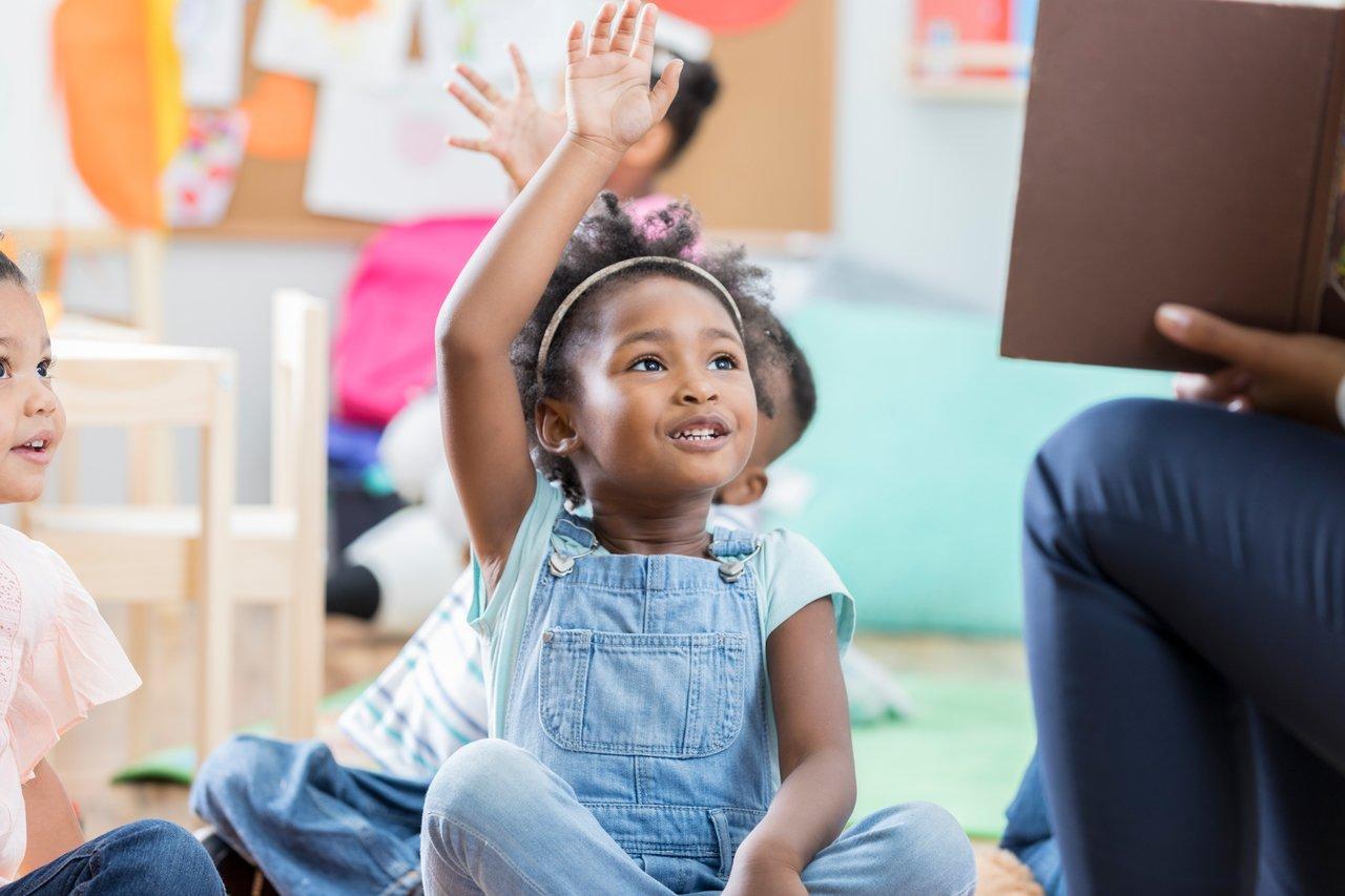 Criança levanta o braço sentada no chão de uma sala de aula