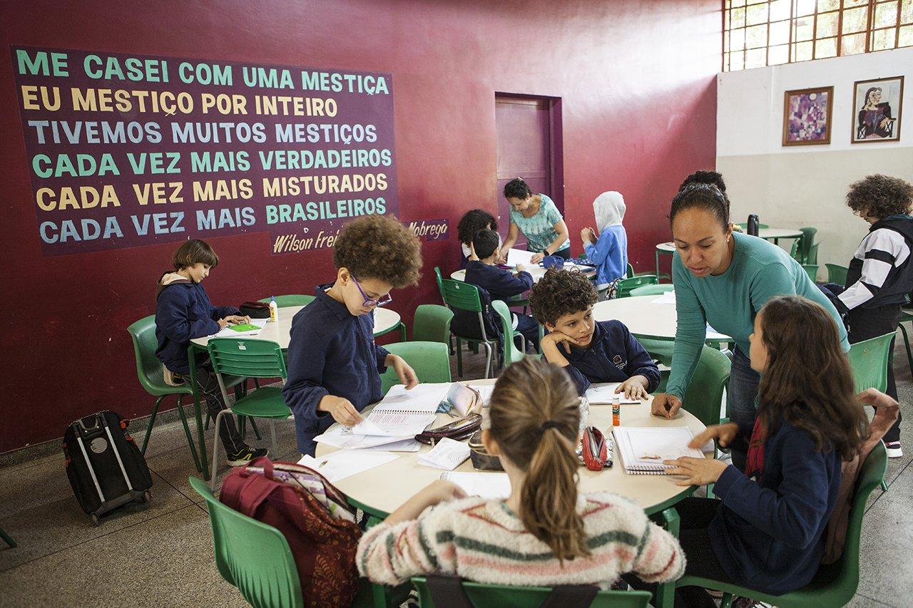 Alunos trabalham em grupo com a ajuda de uma professora tutora na escola Desembargador Amorim Lima, em São Paulo