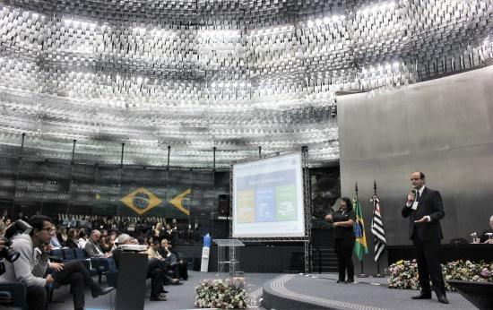 Foto lateral do palco e plateia. Rossieli Soares está de pé. Ao seu lado tem um slide que apresenta a Base
