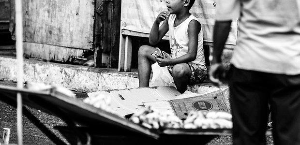 Sem vaga na escola, Pedro* ajuda a mãe na feira e ganha para tomar conta de motos. Sérgio Ruiz