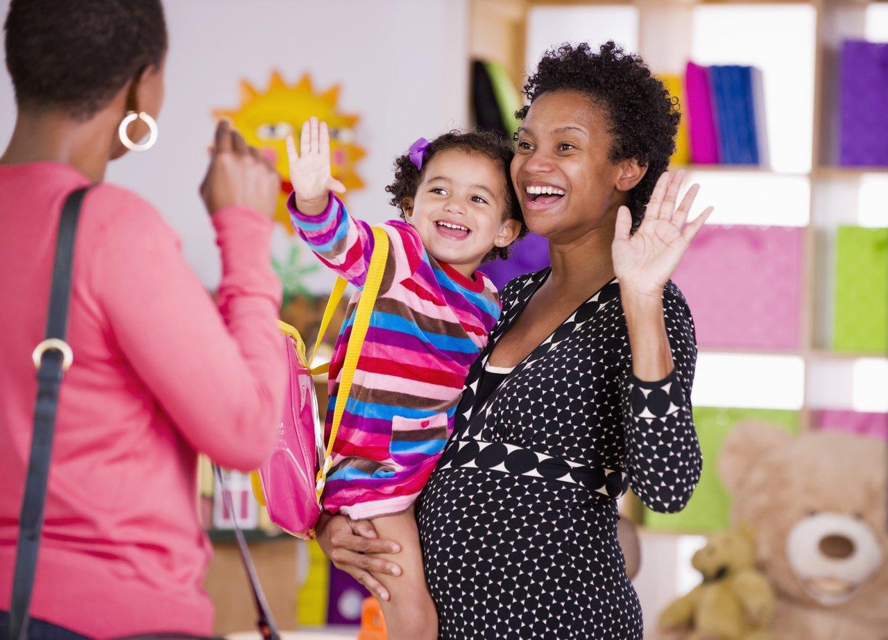 Professora em sala de aula recebe aluna da Educação Infantil no colo e se despede da mãe