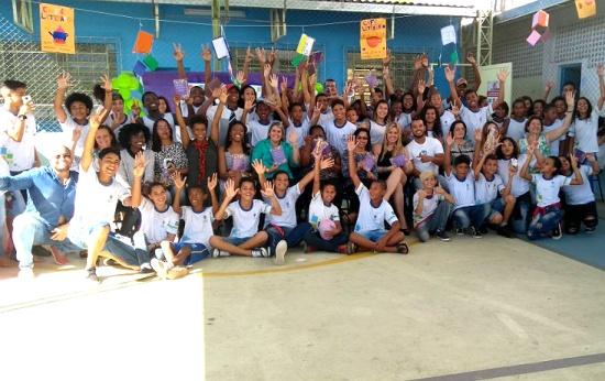 Professores e alunos celebram no pátio da escola