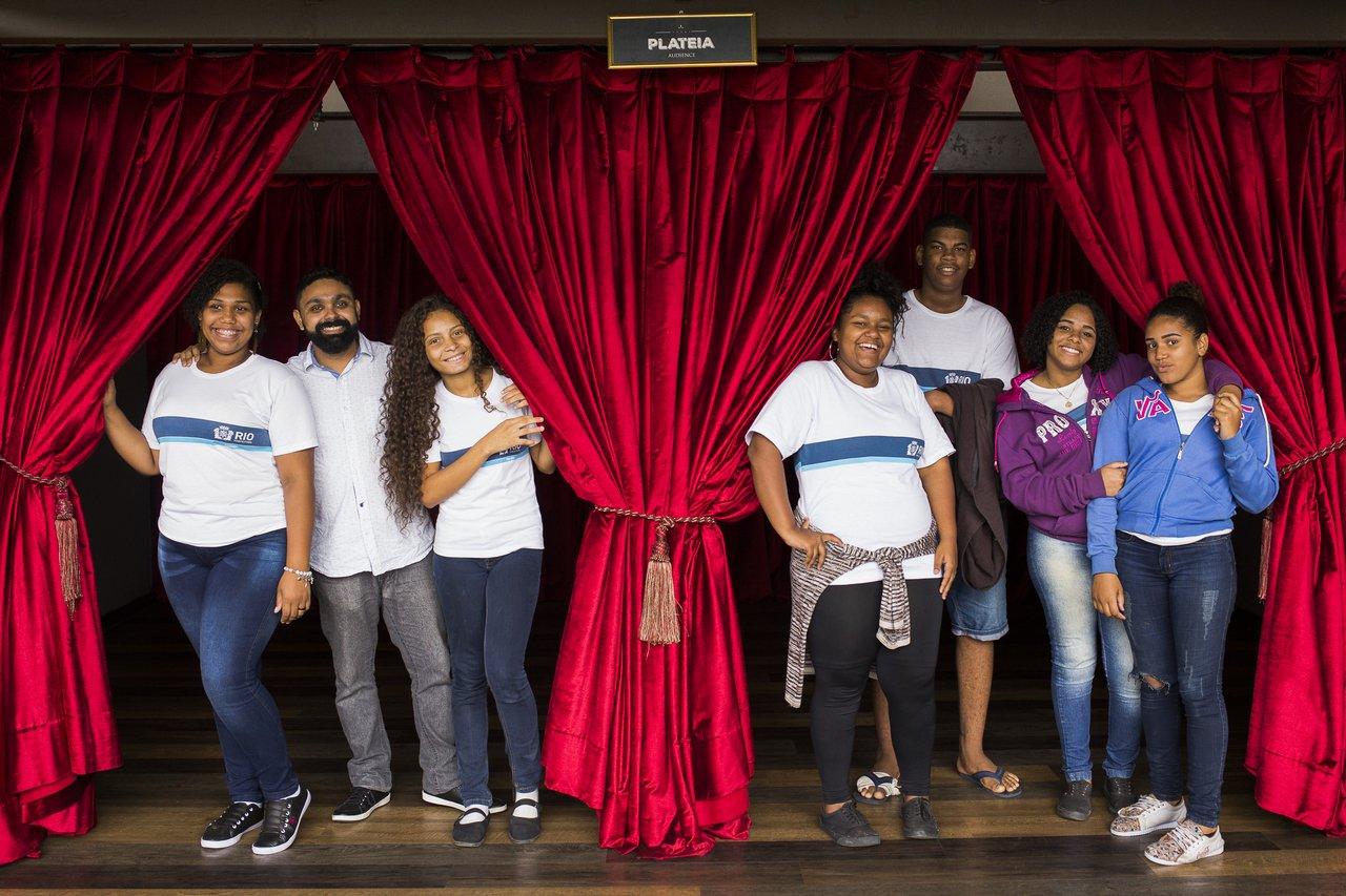 Professor José Marcos Couto Júnior e os alunos do Projeto As Caravanas: Limites da Visibilidade, em um palco de teatro no Rio de Janeiro, brincando com as cortinas