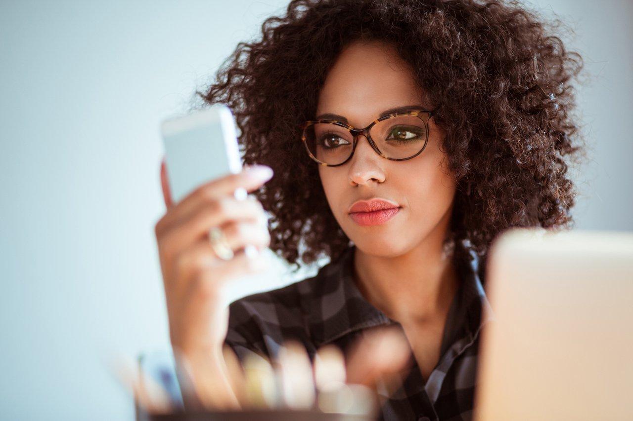 Mulher de óculos em uma mesa, com um computador aberto, olha também para o celular