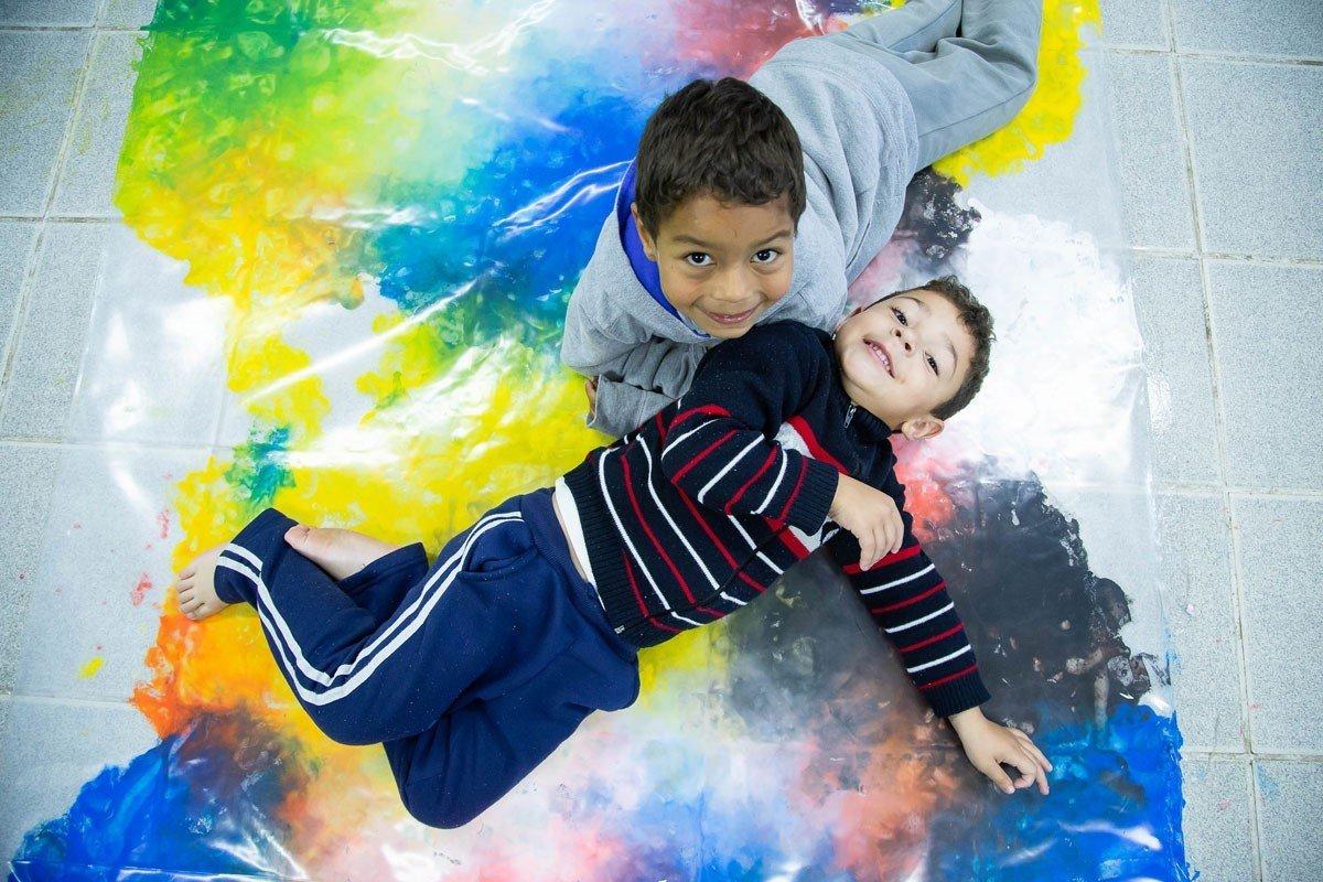 Meninos brincam sobre o tapete mágico, em que é possível misturar tintas conforme se movimentam, formando novos desenhos e combinações por baixo do plástico
