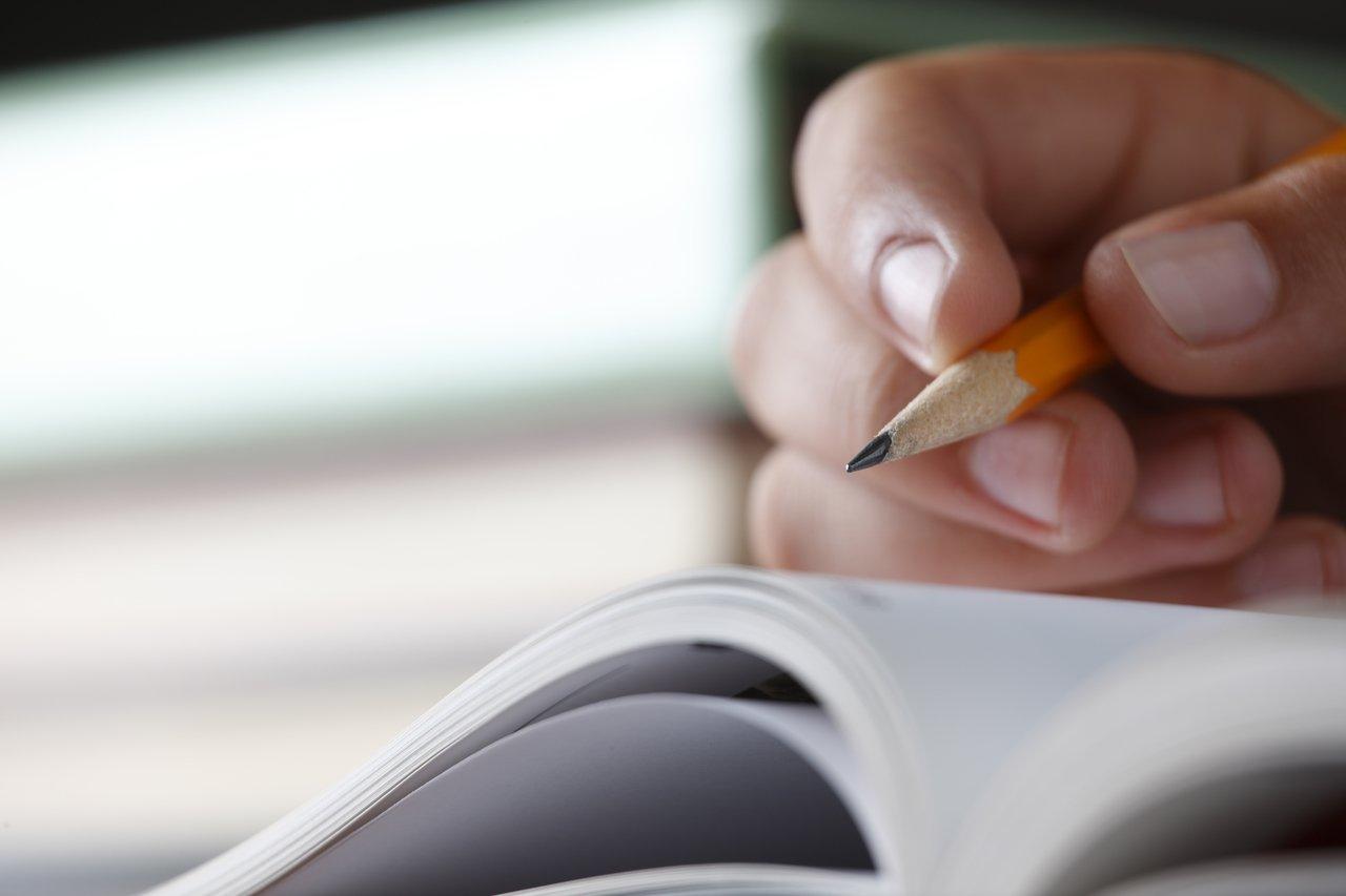 Imagem de uma pessoa escrevendo a lápis