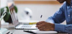 Foto de um homem de camisa listrada na frente do computador, anota em caderninho