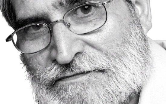 Imagem em close de um homem de 50 e poucos anos, branco de óculos e barba.