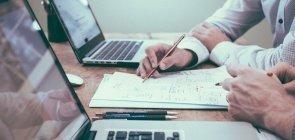 mesa de madeira com dois laptops abertos e os braços de duas pessoas escrevendo em cadernos