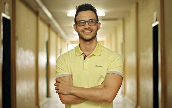 Retrato do professor Wemerson Nogueira de braços cruzados no corretor da escola
