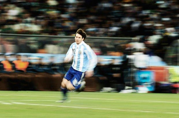 Esta imagem reforça o movimento do jogador em vez de congelá-lo. Para obter esse efeito ao retratar Messi na Copa do Mundo de 2010, o fotógrafo usou uma velocidade baixa na câmera, algo possível em equipamentos profissionais. Foto: Alexandre Battibugli