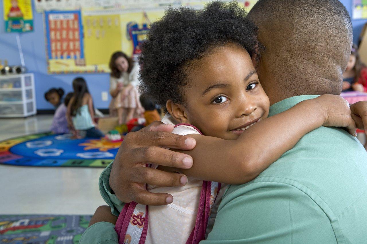 Aluna em primeiro plano olha para a câmera enquanto abraça o pai em uma sala de aula da Educação Infantil