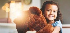 Menina abraçada com ursinho de pelúcia