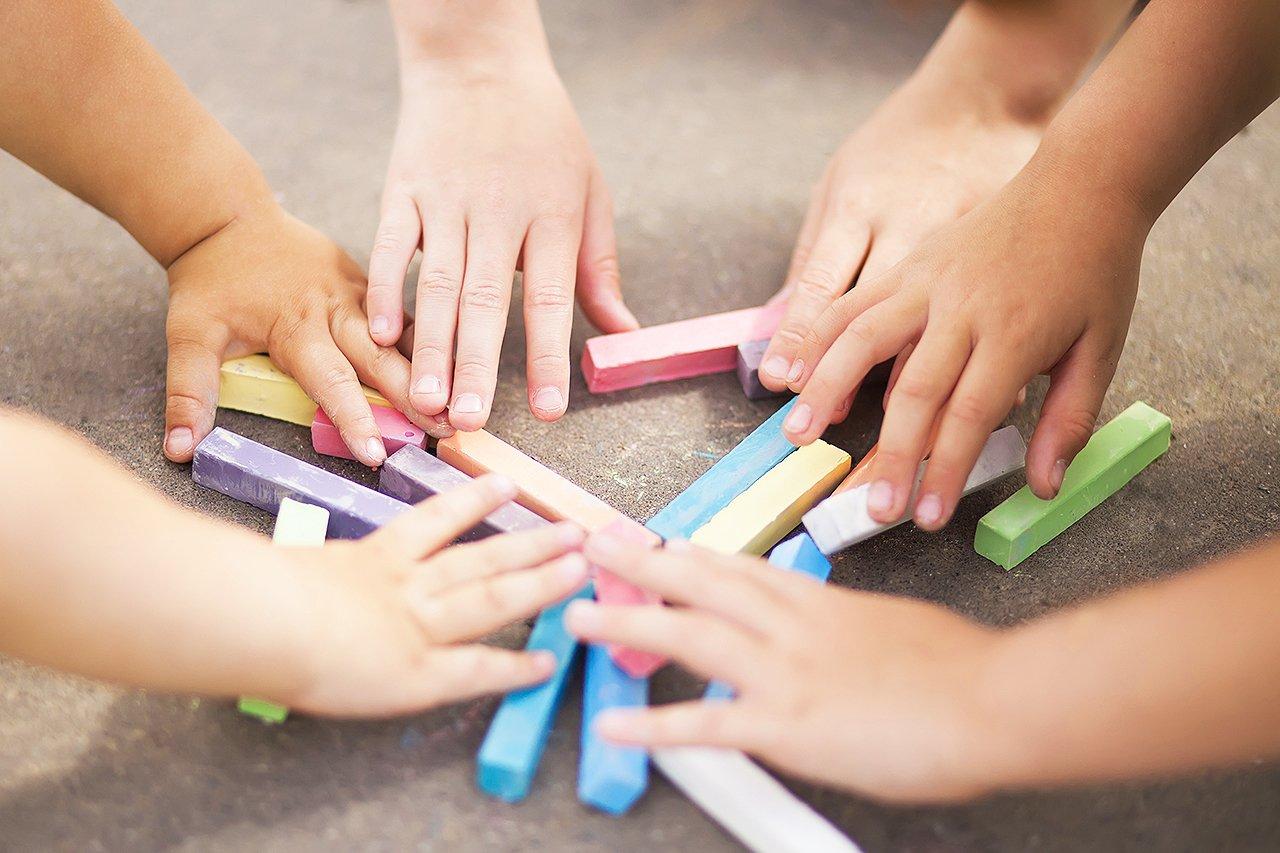 Mãos pegam giz colorido