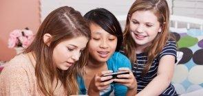 Três meninas olham para celular