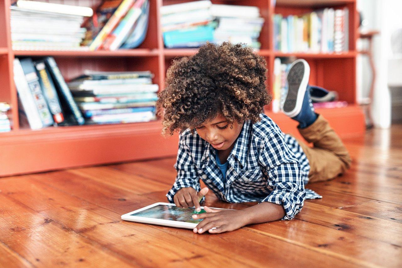 Criança deitada no chão de madeira do que parece ser uma sala ampla está distraída e de cabeça baixa em cima de um tablet