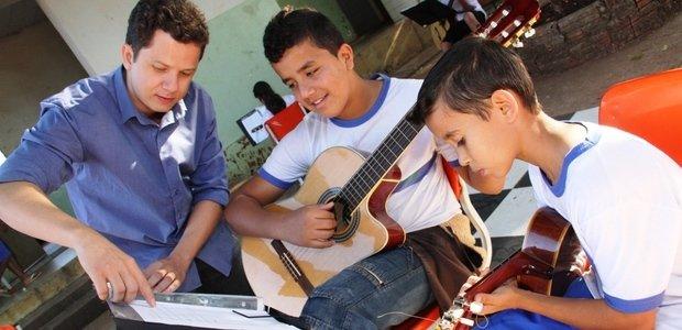 À medida que os alunos iam estudando as músicas de Cartola no pátio da escola, Alessandro passava por todos, tocava junto, tirava dúvidas e orientava os estudantes na prática. Foto: Marco Monteiro
