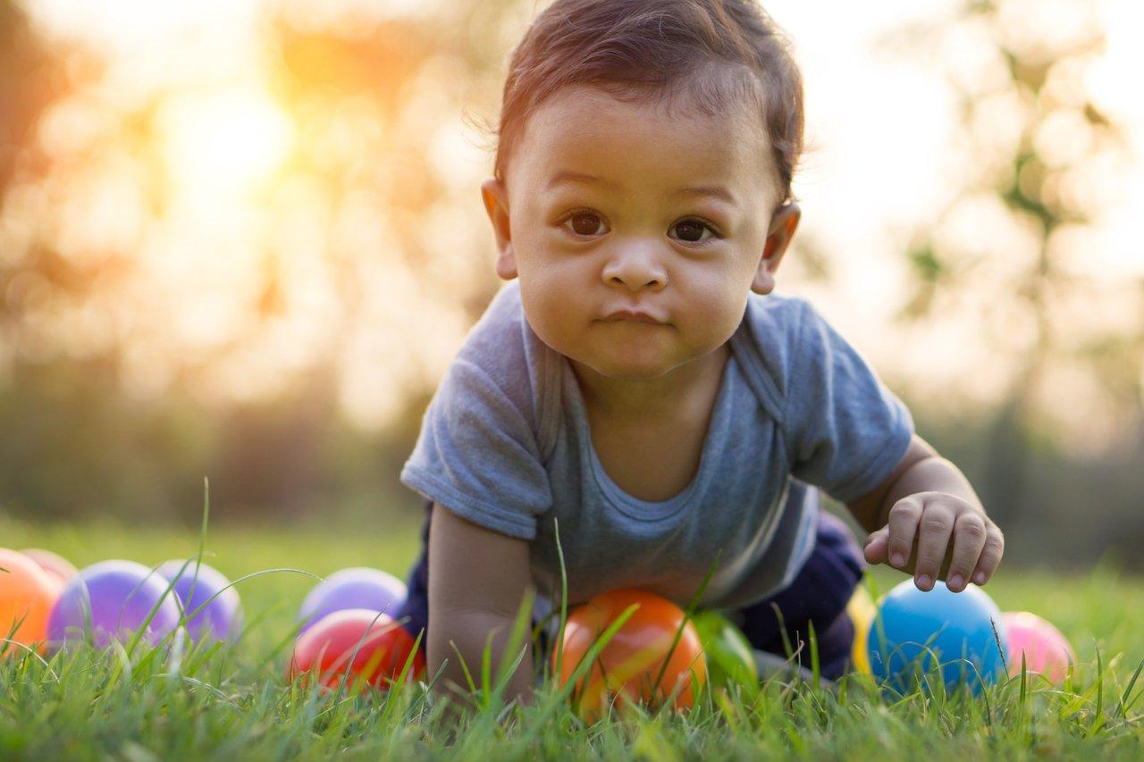 Bebê de bruços e olhando para a câmera, brinca na grama com bolas coloridas