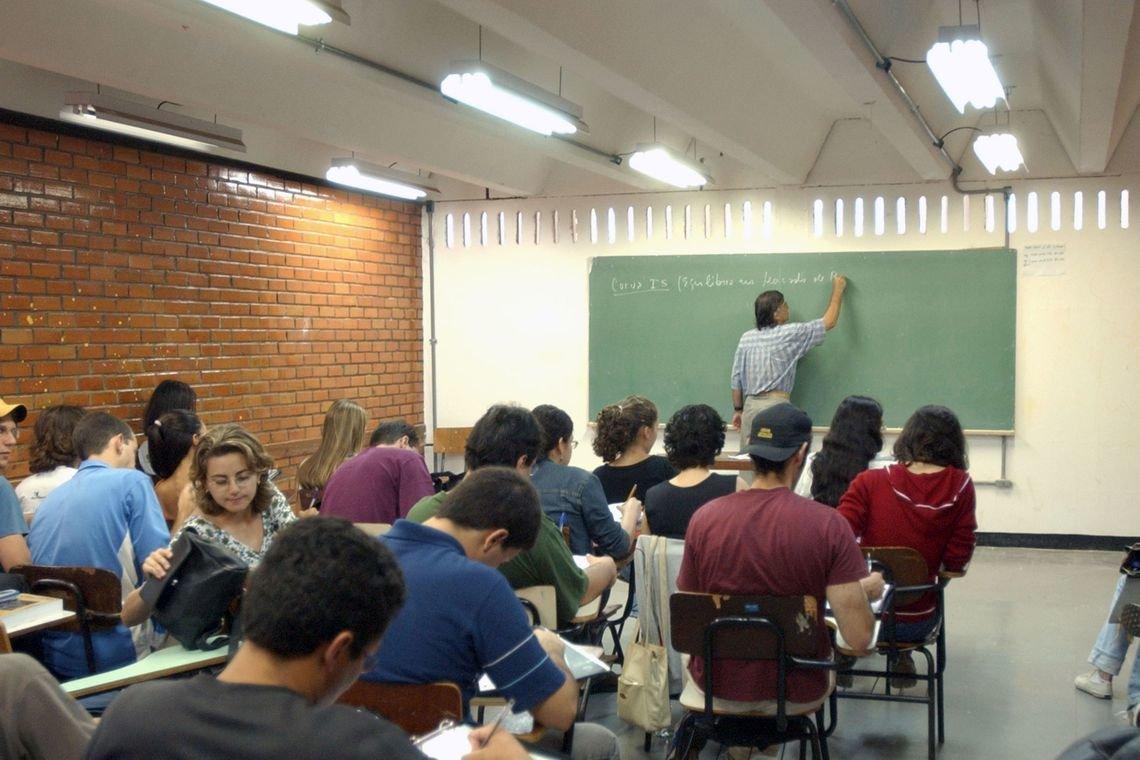 Alunos de Ensino Médio sentados de costas para a câmera em uma sala de aula onde o professor escreve em uma lousa verde