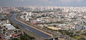 Rio Tietê visto de cima com as pistas da marginal correndo em parelelo. É possível ver diversas construções e carros