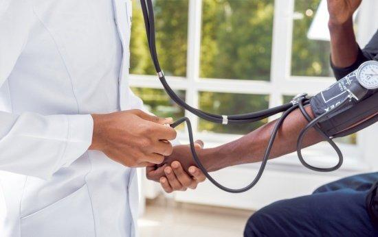 Médico examina paciente. Apenas aparecem as mãos e o estetoscópio