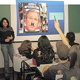 Luciana projeta para a turma a montagem em que Bush usa bigode de Hitler e a charge animada: humor e imperialismo. Foto: Valter de Paula