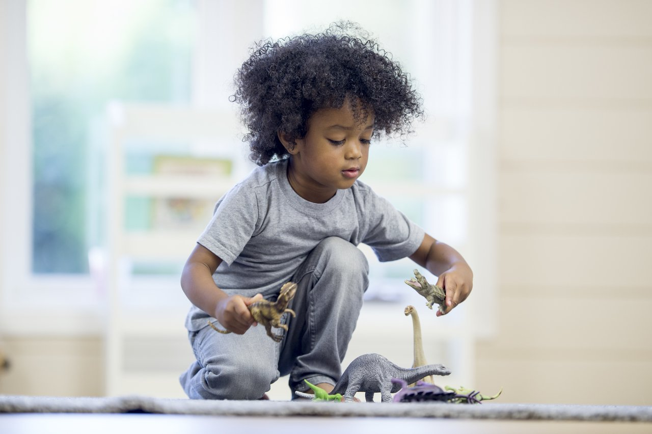 Criança brinca sozinha no chão de uma sala com dinossauros de brinquedo