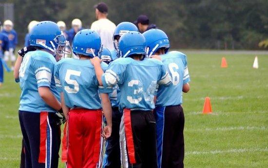 Crianças se preparam para jogar futebol americano em escola
