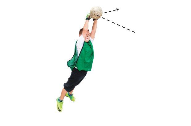 Com as mãos fechadas e unidas, o goleiro dá um soco na bola que vem do ataque