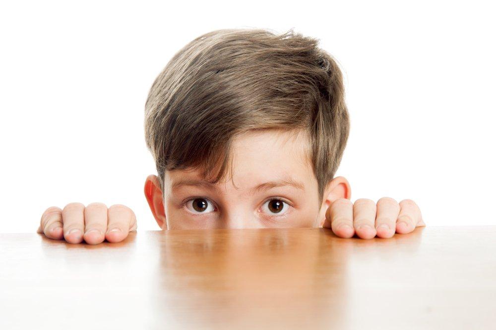 Imagem de um rosto de menino, só dos olhos para cima. O menino está abaixado, se escondendo atrás de uma mesa com os dedos em cima da mesa