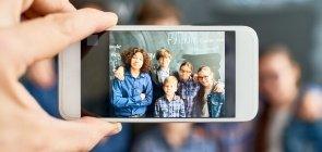 Um celular enquadra alunos em sala de aula, em frente a um a lousa verde, para uma foto
