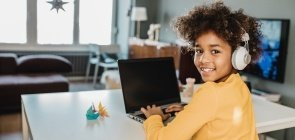 Menina adolescente no computador utiliza fone de ouvido