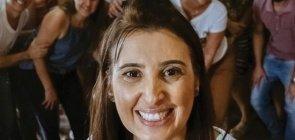 Professora de camiseta branca sorrindo para a câmera, no fundo embaçado um grupo de adultos